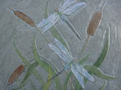 This dragonfly design is relief carved into a natural slate tile and painted with acrylic paint. Painting and carving is sealed on a 11 1/2 x 11 1/2 inch slate square. picture was carved and painted by Dianne Hillesland.