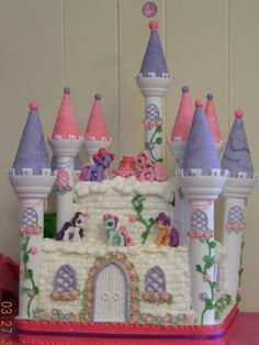"""Ponyville Castle - My daughter wanted a My Little Pony cake for her 3rd birthday, so I went to the only place I go to for inspiration, CAKE CENTRAL, and here we have it. This cake was inspired by a cake by """"meharding"""" so meharding thank you so much for your beautiful cake it was truly an inspiration. The top tier is raspberry and cream cake, while the bottom is a yellow pound cake. Both tiers are iced with buttercream icing."""