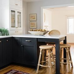 """Black lower cabinetry and white upper cabinetry is the key to a classic """"tuxedo"""" kitchen. Adding woven bistro stools from Serena & Lily and a vintage rug runner softens and warms up the whole space. Design: Trim Design Co. Photography: Joyelle West  #kitchendesignideas #blackandwhitekitchen #shakerkitchen"""