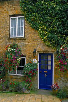 England    Blue Door and Hanging Flower Baskets