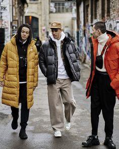 Gelb: Er trägt eine schwarze, lockere Hose und einen schwarzen Hoodie. Dazu trägt er eine Bodybag und eine lange, gelbe Daunenjacke.  Schwarz: Er kombiniert eine relaxed Jeans mit einem weißen Hoodie und einer schwarzen Daunenjacke. Zusätzlich trägt er eine Cap.   Rot: Er trägt ebenfalls eine schwarze, weite Hose und einen weißen Strickpullover. Die Eye-Catcher seines Looks sind die Umhängetasche und die rote Jacke. Weekday Jeans, Blue Denim, Winter Jackets, Fitness, Men, Fashion, Baggy Trousers, Black Hoodie, Jackets