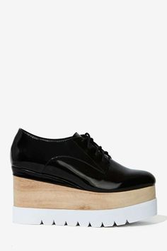 These black box leather oxfords have lace-up detailing, a rounded toe, and a white lug sole with wood at center.