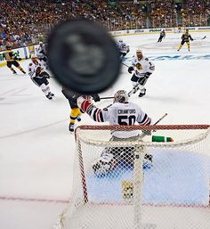 SI Pictures of the Year - The puck flies over Chicago Blackhawks goalie Corey Crawford in game 3 of the Stanley Cup Final against the Bruins.