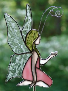 This delightful stained glass garden fairy is crafted from a beautiful shade of opalescent pink glass with accent colors of peach, gold, and clear glue chip for the wings (this pretty glass looks like frost on a window). She is detailed with hand formed wire accents and a delicate