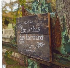 A natural wood sign with distressed print guided guests to the spot where Lindsey and Jeff said their vows.