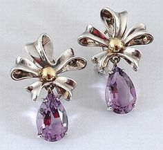 A pair of silver gold and amethyst drop earrings by Tiffany & Co., circa 1990, each claw set with a pear cut amethyst suspended from a sterling silver ribbon and bow with 18ct gold knot and post fittings hallmarked boxed