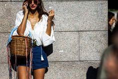 woman wearing denim shorts and basket bag before fashion show