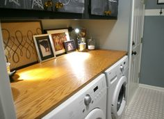 Lay Out a Folding Station  When working in a smaller laundry room or nook—every inch matters. Take advantage of the space above two front-loaders by installing a wood countertop; Bryn Alexandra bought and cut plywood at Lowe's to serve as a countertop for folding clean laundry.