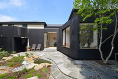 An extension of a Victorian House in Melbourne by Thomas Winwood | a dark stained curvilinear wall projects from the existing structure