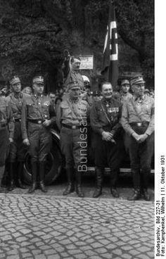 Bad Harzburg.- Gründung der Harzburger Front, Vorbeimarsch der SA-Verbände vor Adolf Hitler nach Beendigung der Tagung, Hitler im offenen Auto stehend, vor ihm Ernst Röhm, rechts neben Röhm Hermann Göring und links Viktor Lutze.
