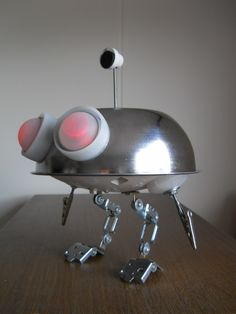 "Last week I found a metallic housing from a lamp. Lucky of me, it has two holes. First thing I thought? The ""*Batteries Not Included"" movie! (Big surprise...) So, for the umpteenth time, lets make a BNI inspired junkbot. It's easy, it's fast and it's an original and useful gift for Christmas. It lights its eyes, has a magnet in its antenna for keep clips and you can keep memos in its tweezers."
