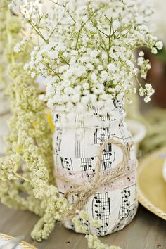 Wrap bottles in musical note paper and fill with baby's breath for wedding centerpiece idea