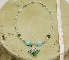 Beaded anklet ankle bracelet made with semi precious aqua blue luster jade round side beads, dangles made with light aqua blue and olive Swarovski Crystals hanging off of a large round twisted ring, and matching Czech glass beads and twisted tube beads around sides. All silver metal beads are lead/cadmium-free pewter; clasp and other finishing-off pieces are sterling silver-plated.    The colors on this anklet are very vivid in true form. Olive green and blue (no matter what shade) alway...