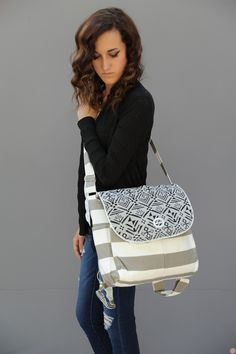 You'll love the functionality of this amazing Bag. Grey and white bold stripes with a grey and black aztec print. A cute white button in front...