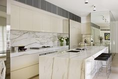 david hicks kitchen--waterfall marble island, mirrored storage, off white lacquered cabinetry