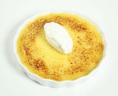 A photo taken looking down on Lemon Pudding baked and brûléed and topped with quenelle of Crème Chantilly.