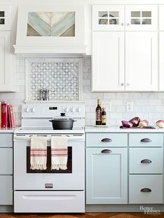 2 tone cabinets Tile can add a raised facet to a space to help boost visual interest. in this pastel kitchen, the backsplash tile -- a miniature mosaic bordered by a raised tile -- picks up on the cabinet details and offers a focal point behind the range. Blue Kitchen Cabinets, Kitchen Redo, New Kitchen, Kitchen Makeovers, Upper Cabinets, Kitchen Tile, Kitchen Countertops, Kitchen Renovations, Kitchen Ideas