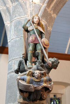 1c : Saint Michel terrassant le dragon. Kersanton polychrome, XVe siècle, h=1m. Nef, à l'entrée du choeur, contre le pilier de gauche ; statue en kersanton du XVe siècle sur un socle en pierre représentant un ange. L'ange embrasant un demi-cercle dont je n'identifie pas le sens est remarquable ; je note sa coiffure, à raie médiane, ou la richesse de sa robe aux emmanchures ornées. L'archange est également admirable, mais le dragon grimaçant, cornu et griffu qui lui agrippe la jam...