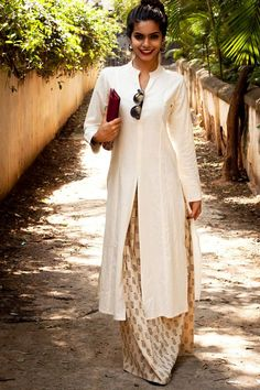 Slit Kurta in off white soft cotton with pleated skirt in cream black block.(The…