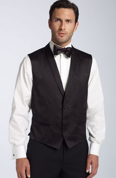 The BOSS Black line prepares you for a big night out with this elegant three piece tuxedo. Wool construction goes with a unique modern design on this tux. Instead of a peaked lapel, a notched lapel and two button construction is featured. The lapels are faced in satin, with the shawl collar vest featuring a…