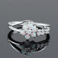 Opals and cubic zirconia stones create a beautiful floral motif on this sterling silver ring, while more cubic zirconia stones accent the band. RING DETAILS - Surface width: 8 mm - Metal: sterling sil