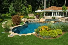 This lush back yard features a bold mixture of greenery and purposeful landscaping along with an oblong pool at center, wrapped in a low stone wall. Jacuzzi sits on a raised patio just above.