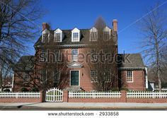 Vintage three story red brick house with white fence
