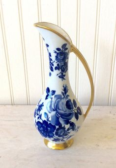Beautiful porcelain flower vase with blue roses & gold trim. Stamped on bottom Delft 1103, Kunst Bavaria. Kronach with crown design & engraved # 126/3. In very good vintage condition no chips or cracks. Lovely vase for any small flower arrangements or single stem rose. Will ship insured & packaged carefully!  Measures 7.75 height x 3.25 diameter towards base x 3.5 at widest point x 1 opening for stems. Thanks for shopping YellowHouseDecor!   Several Delft Blue items sold in...