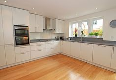 Large L-shaped kitchen in a white satin lacquer finish.