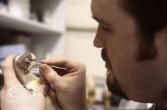 Trevor L. Hensley adds fine detail to PAULIE's parrot puppet.