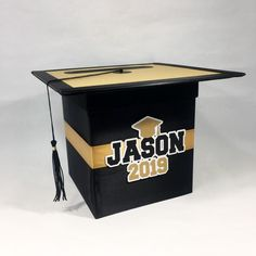 """Black, gold, and white graduation cap style cardbox with a tassle. The box dimensions are x x and is made from cardboard. I can include your graduate's name on the front of the box or I can leave it at """"Congrats GRAD"""". Graduation Card Boxes, Graduation Party Planning, College Graduation Parties, Graduation Party Decor, Graduation Gifts, Graduation Bouquet, Graduation Centerpiece, Graduation Ideas, Grad Party Decorations"""