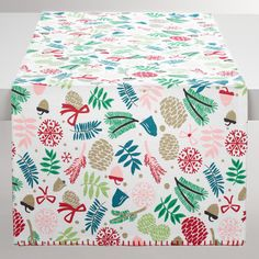 Crafted of cotton with blanket stitching on the ends and a solid red backing, our exclusive runner is printed with pine branches, bows, acorns, snowflakes and more. Set a bright and colorful holiday table at an affordable price by layering with our coordinating napkins and placemats.