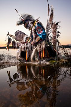Mi'kmaq warrior and dancer, Danny Boy Stephens, takes a moment to reflect on the shores of the Great Slave Lake, Northwest Territories, Canada.  Lighting info:  used a single Elinchrom studio strobe, positioned to the camera left, bounced into a silver umbrella.  Back lighting is natural (the rising sun).  See the full blog post on this shoot here:  davebrosha.com/2010/08/18/fire-warrior/  join me on Facebook:  www.facebook.com/davebroshaphotography