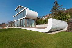 Casas de ensueño: una vivienda futurista con forma de tobogán frente a un lago suizo — idealista/news