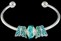 silver plated items: bangle, two enamel beads. One glass bead with 925 silver core.