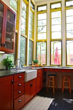 15 Farmhouse Sinks for Every Kitchen Imaginable - red wood, yellow windows, black counter, white sink