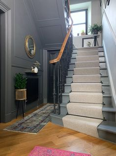 Grey walls with black doors are brought to life with brass accents and a pink rug. Original Victorian balustrade has been returned to its original splendour in black cast iron. a diagonal herringbone oak floor adds further character. Hallway Designs, House Design, Victorian Hallway, House Inspiration, Home, House, Stairways, New Homes, House Staircase