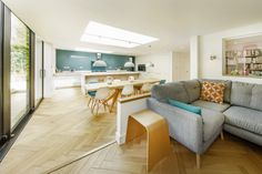 Raised snug area with a grey corner sofa overlooking the open plan kitchen/dining area. A vivid blue splashback provides an accent of colour that is picked up again at the large wooden dining table with the coloured Eames chairs.