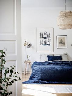 Swedish bedroom with an IKEA chandelier, large framed art, and blue bedding
