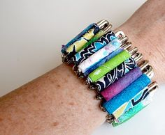 Cute bracelet made with safety pins and rolled fabric.  I think paper beads would be cuter, but good idea!