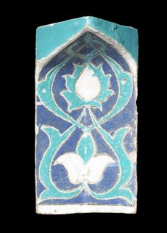 A Timurid cuerda seca pottery Squinch Tile (muqarna)  Samarkand, 14th Century of rectangular and concave form with pointed arched top, incised and decorated in cobalt blue, turquoise and white with a palmette and a flowerhead flanked by foliate motifs  30 cm. high x 18cm. wide