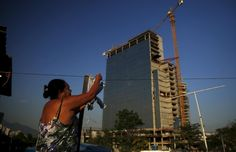 A resident of the Vila Autodromo favela picks up her clothes in front of the construction work for the Rio 2016 Olympic Park in Rio de Janeiro, Brazil June 9, 2015. Residents have been threatened with eviction and required to move due to the construction work for the Rio 2016 Olympic Park, and about half have so far accepted compensation offers and left. The land conflict in Vila Autodromo, which feels like a ghost town with 90...