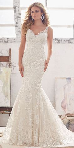 This Beautiful Fit & Flare Wedding Dress Features Frosted Alencon Lace Appliqués on Net with an Eye-catching Wide Scalloped Hemline. Illusion Panels at the Waist Complete the Look. Covered Buttons Accent the Illusion Back.