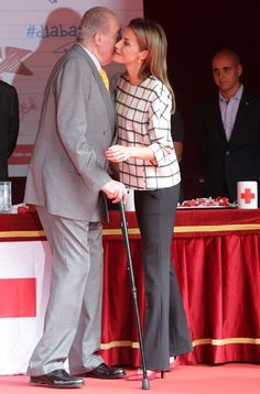 Former King Juan Carlos greets daughter-in-law Queen Letizia as they help at Spain's Red Cross Day 10/8/2014