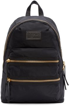 Nylon backpack in black. Gold-tone hardware. Grab handle at top of bag. Two adjustable shoulder straps. Leather logo patch and two zippered compartments at bag face. Two-way zip closure at main compartment. Fully lined. Tonal stitching. Approx. 11