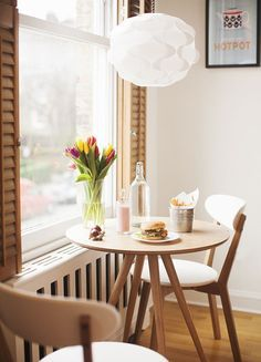Dining Room White Pendant Round Dinette Table White Futon Dining Chair Glass Window Painting Wooden Floor Flower Vase Yellow Tulip Water Bottle Plate Burger Fried Fries Bucket Tiny Dining Room Ideas for People with Small Place to Live