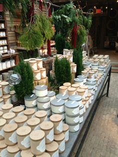 Beautiful candle display. Could be replicated for a table at a craft fair. Love the use of greenery as a prop to warm up the space and break up the candles