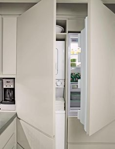 Eric Pike's NYC kitchen features a stacked washer and dryer next to a refrigerator, via Martha Stewart.