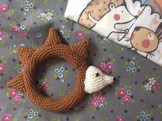 Babyrammelaar Egel: Koker van bruin om oude armband heen haken, 1 toer = 14 vasten. Zoveel toeren haken als nodig is. Beetje opvullen. Eventueel belletje erin doen. Sluiten tot ring. Kopje van ecru; kegel = mr van 4, steeds 2 meerderen tot gewenste grootte. Oogjes, neusje met zwart erop maken, beetje vullen. 4 Stekels, kegel, 7 toeren. Kop en stekels op de ring bevestigen. Klaar!