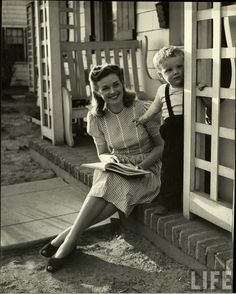"""Mother reading to child in """"American Look"""" for LIFE, May 21, 1945. Photograph by Nina Leen. """"Domesticity. She has pride in her house and her children and the way she looks when she is doing her housework. She likes gay-colored aprons and wash frocks..."""